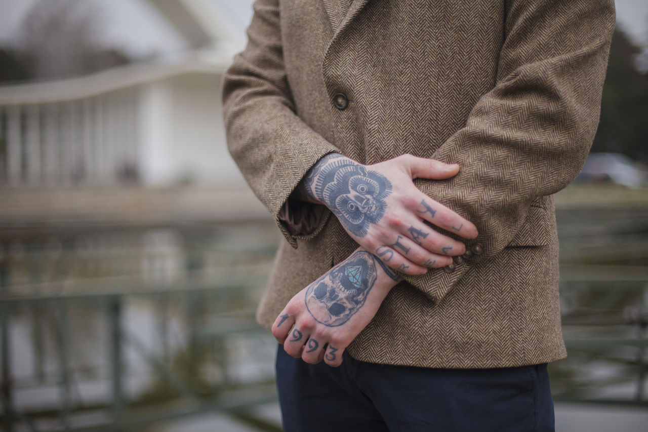 Midsection of young male model with tattoos standing outdoors