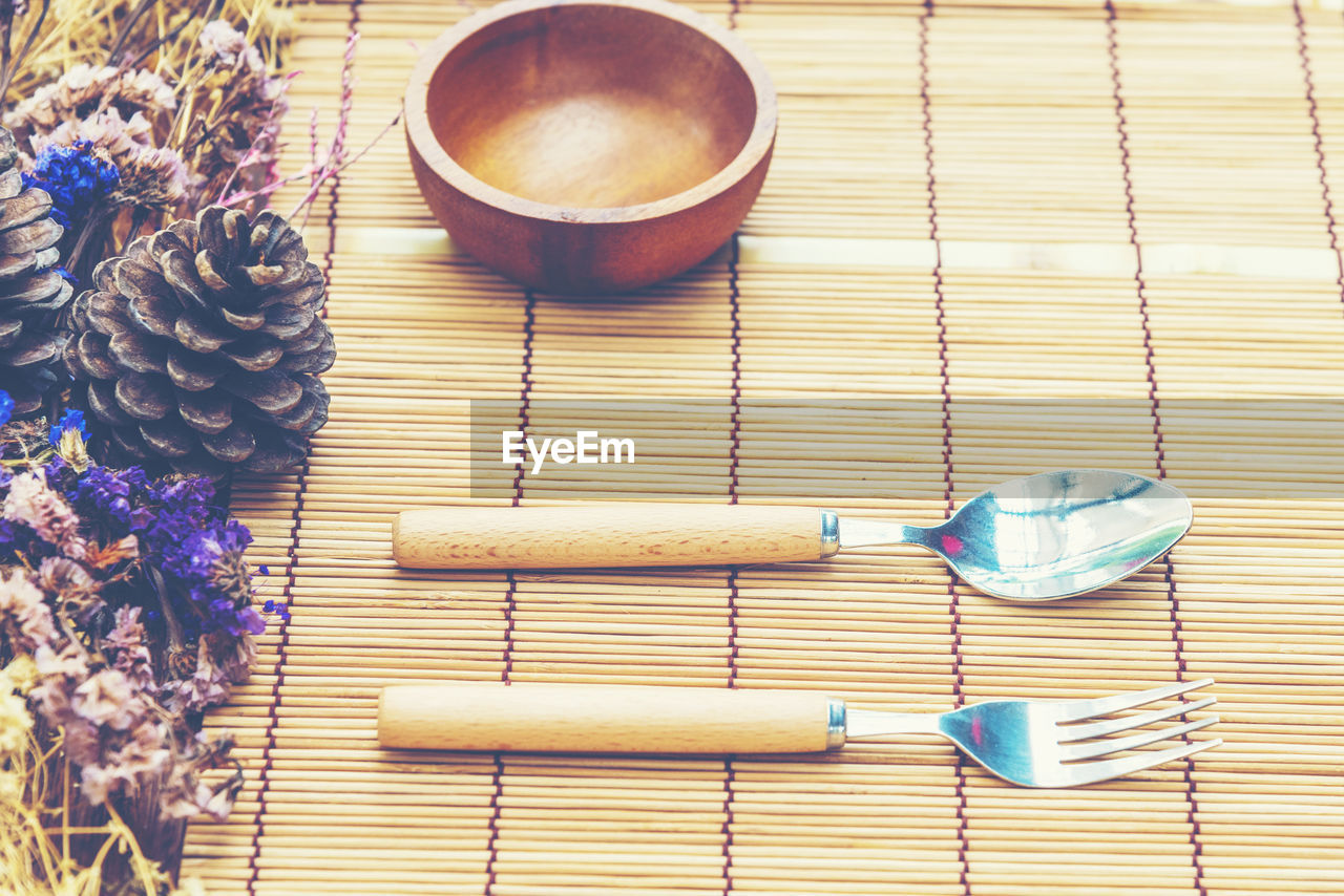 table, food and drink, still life, indoors, food, freshness, no people, high angle view, kitchen utensil, close-up, cup, flowering plant, flower, spoon, eating utensil, refreshment, wood - material, bowl, healthy eating, blue, place mat