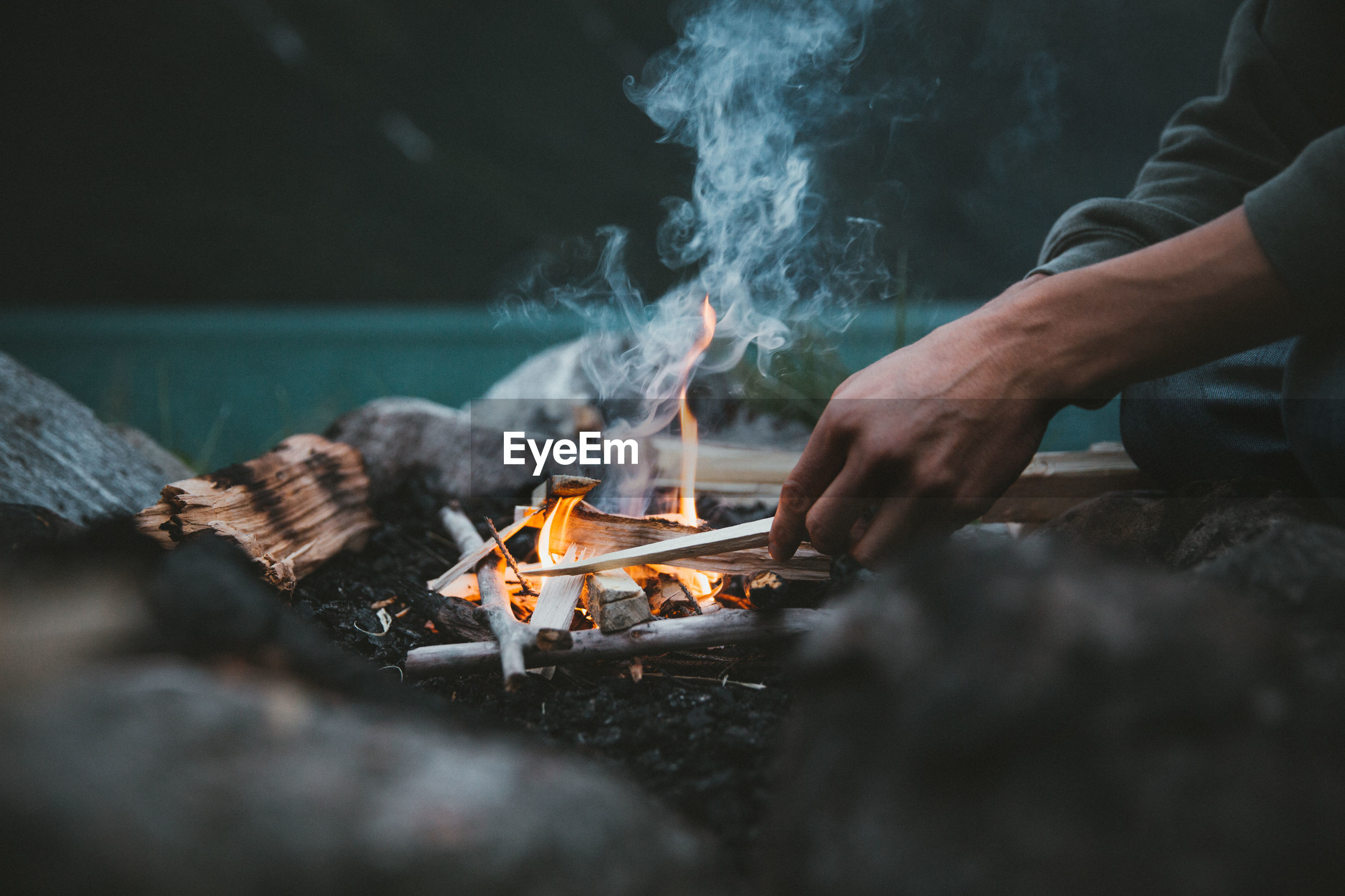Midsection of man sitting by campfire