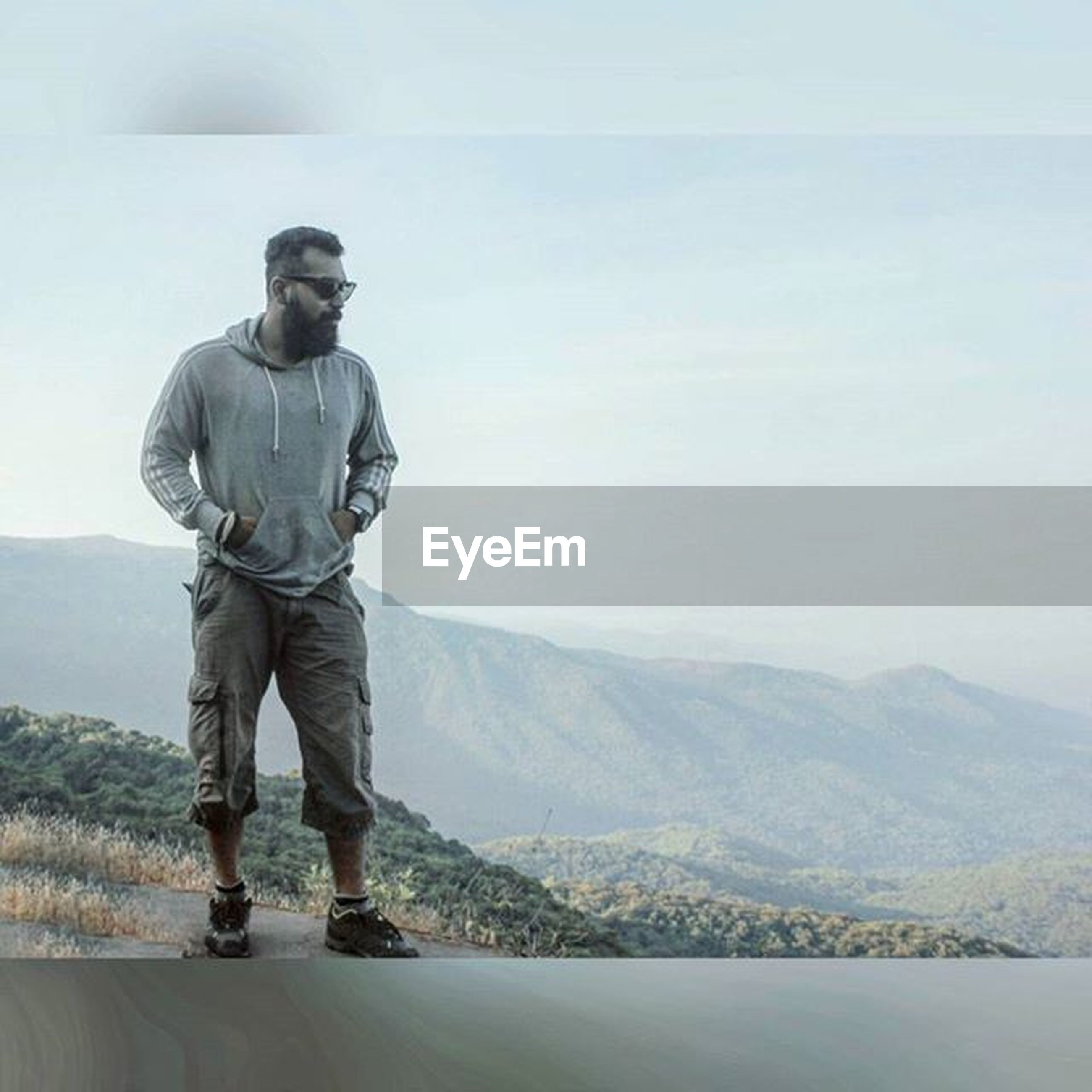 mountain, standing, tranquil scene, tranquility, rear view, lifestyles, scenics, sea, full length, mountain range, nature, leisure activity, casual clothing, landscape, beauty in nature, men, sky, copy space