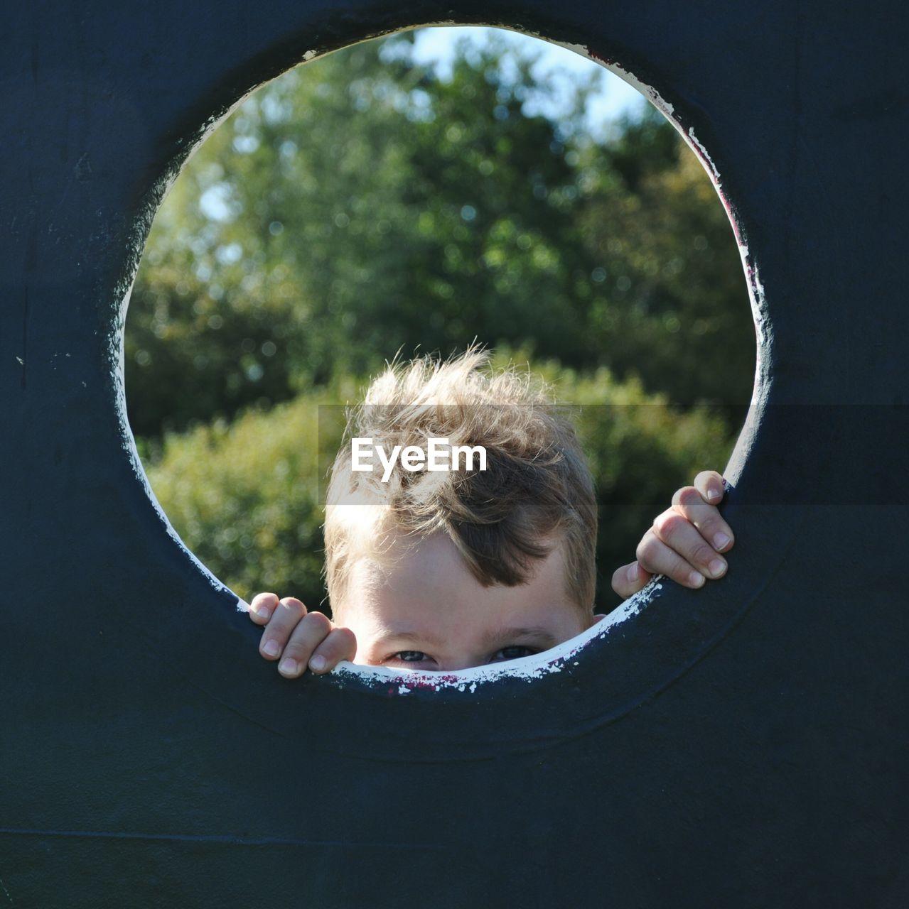 Boy Seen Through Play Equipment