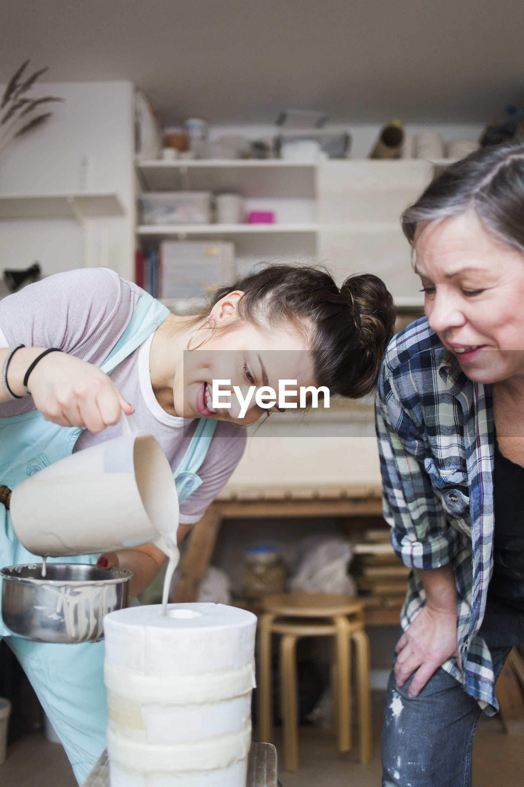 Mature female potter bending while looking at smiling young employee pouring clay from pitcher in vase at workshop