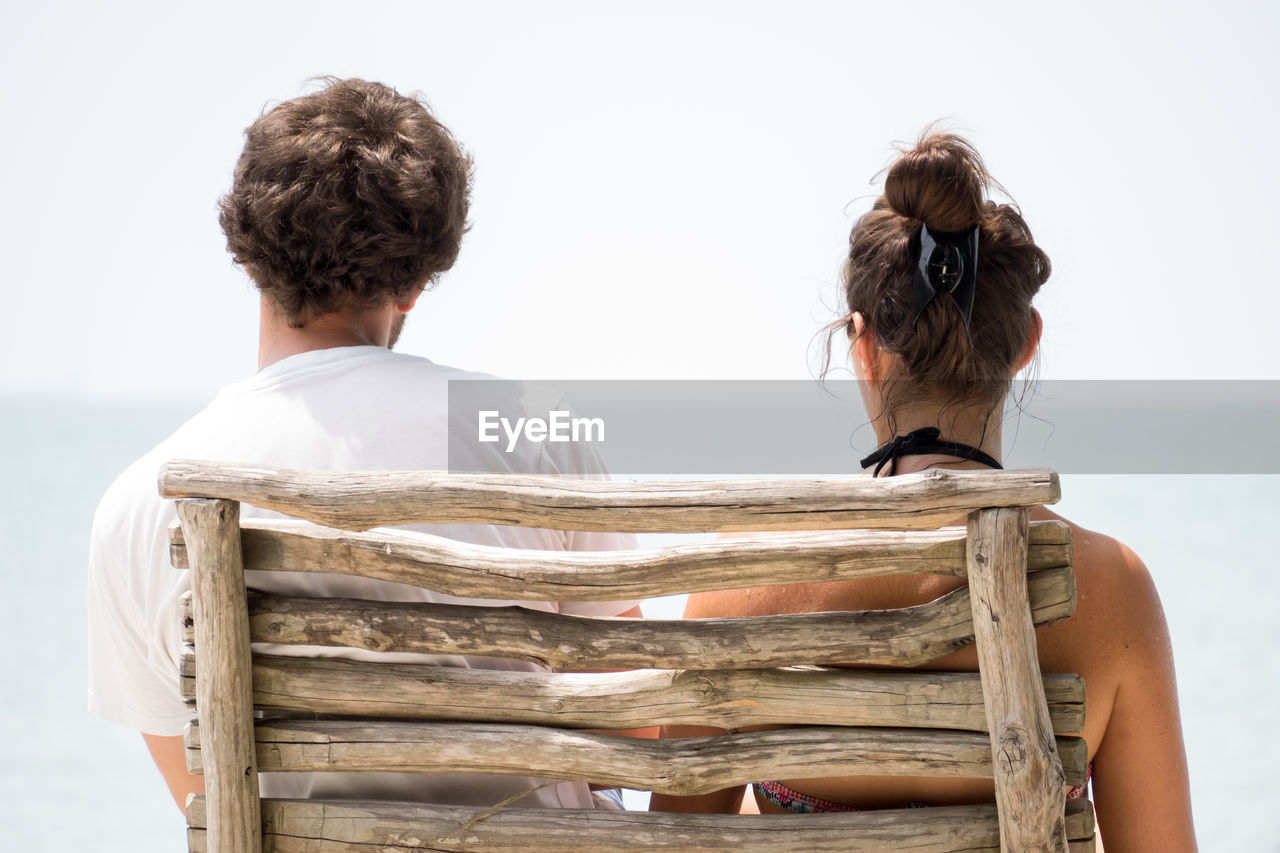 Rear View Of Couple Sitting At Deck Chair Against Clear Sky