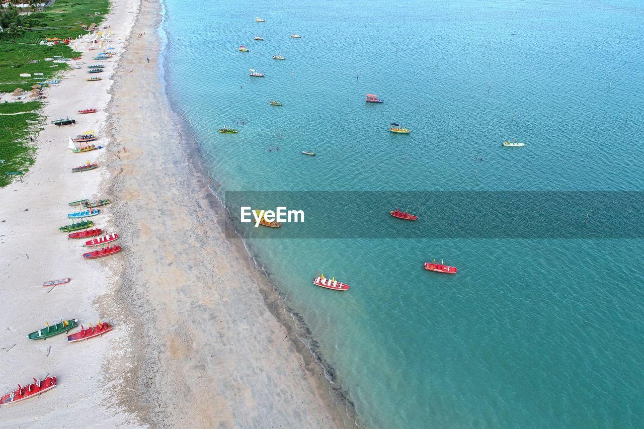water, nautical vessel, high angle view, transportation, sea, aerial view, day, nature, mode of transportation, outdoors, beauty in nature, travel destinations, beach, scenics - nature, land, travel, turquoise colored, holiday, vacations, luxury, sailboat