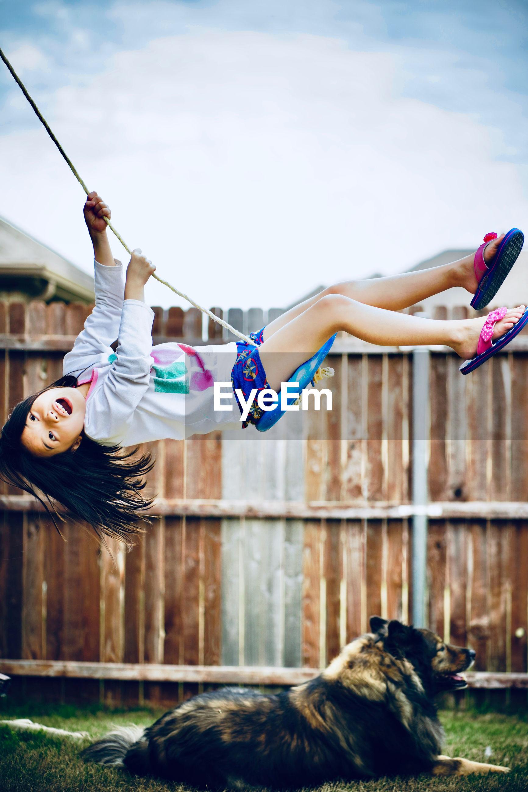 Side view of girl swinging over dog against sky