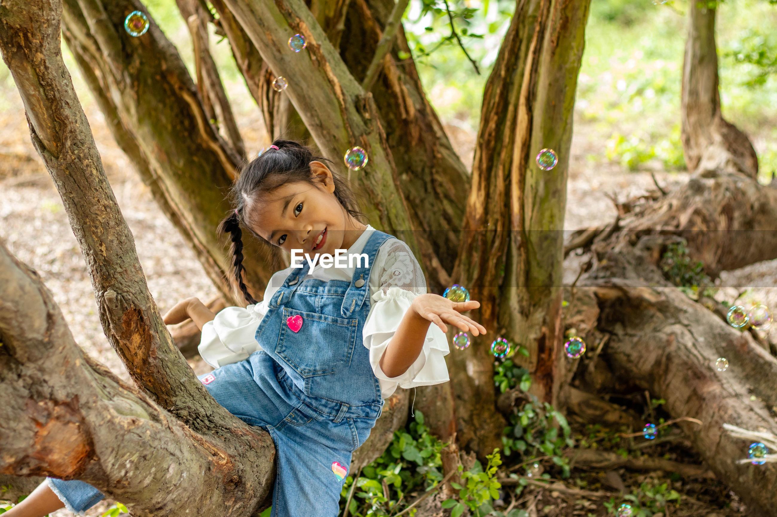 Portrait of cute girl sitting on tree