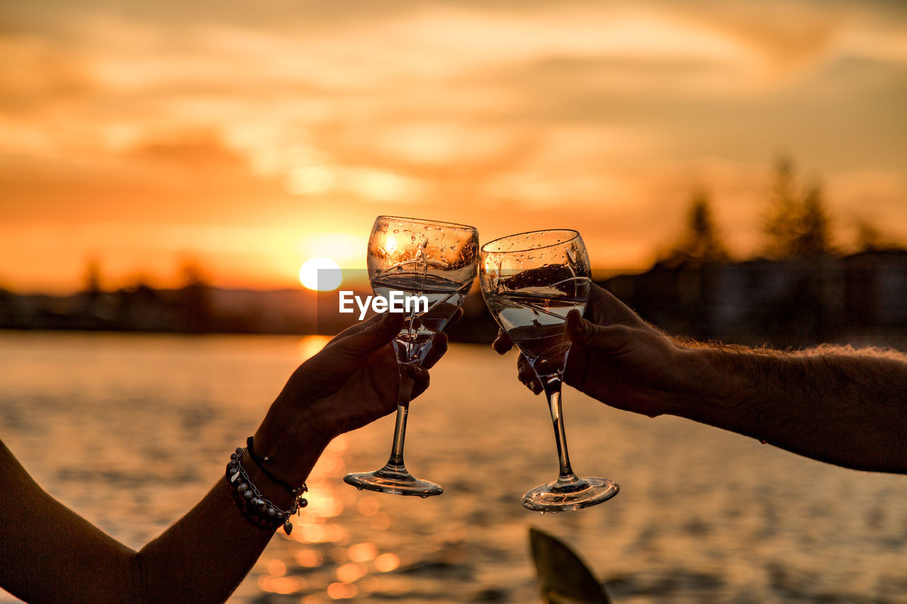 Cropped Hands Of Friends Toasting Alcoholic Drinks By Lake Against Sky During Sunset