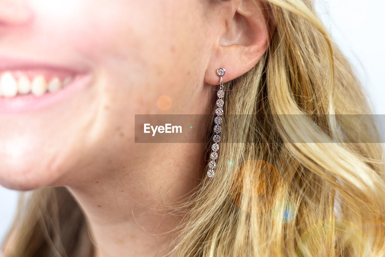 Close-up of smiling woman wearing earrings