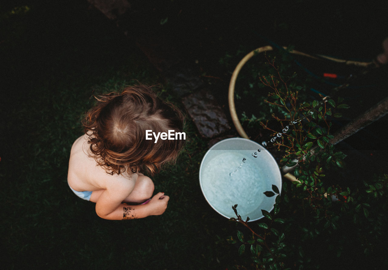 High angle view of shirtless girl sitting by bucket with water