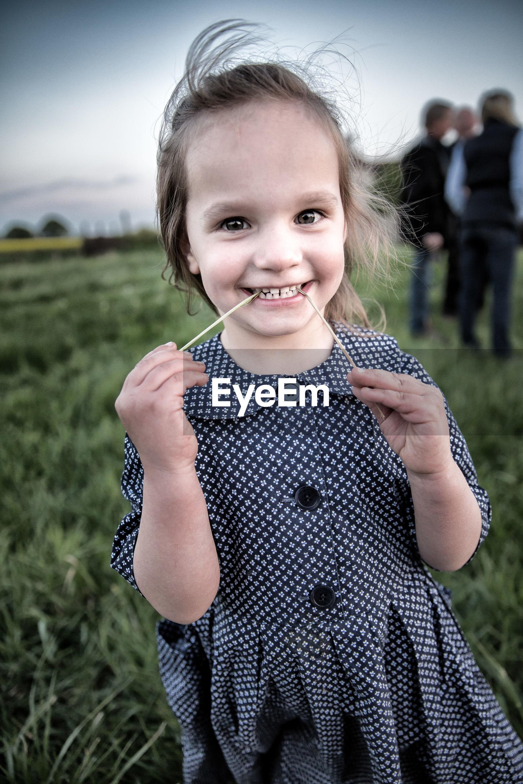 Portrait of smiling girl standing on grassy field