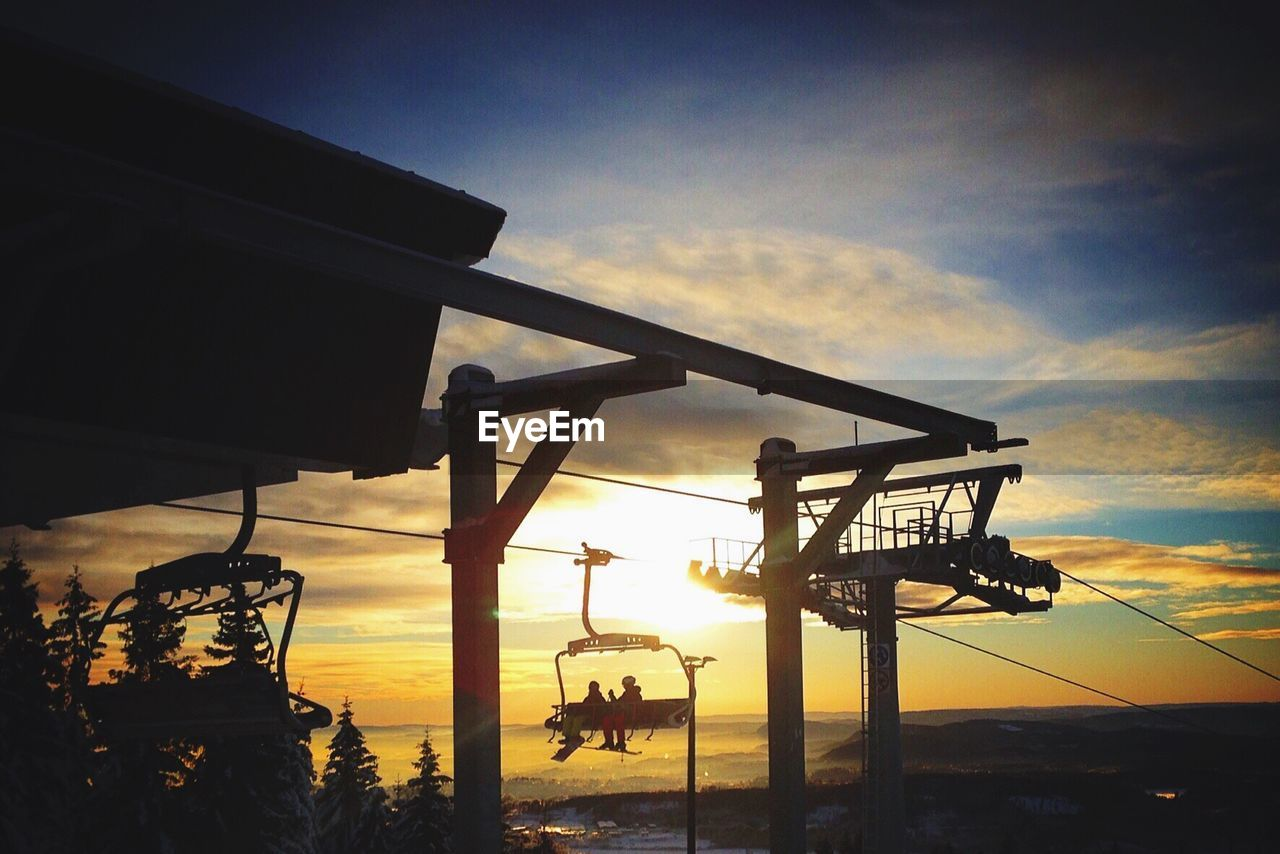 People sitting on ski lift against sky during sunset