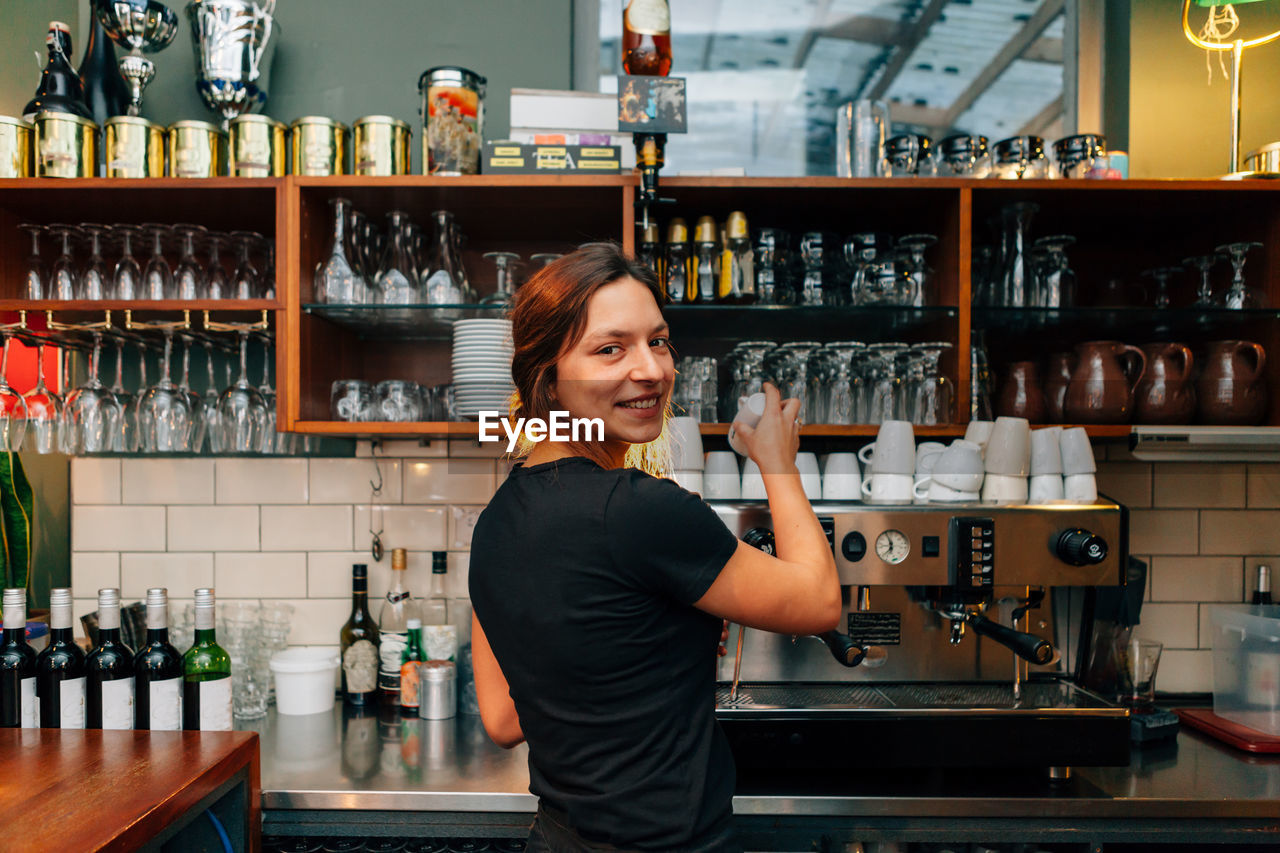 Portrait of smiling woman working in kitchen