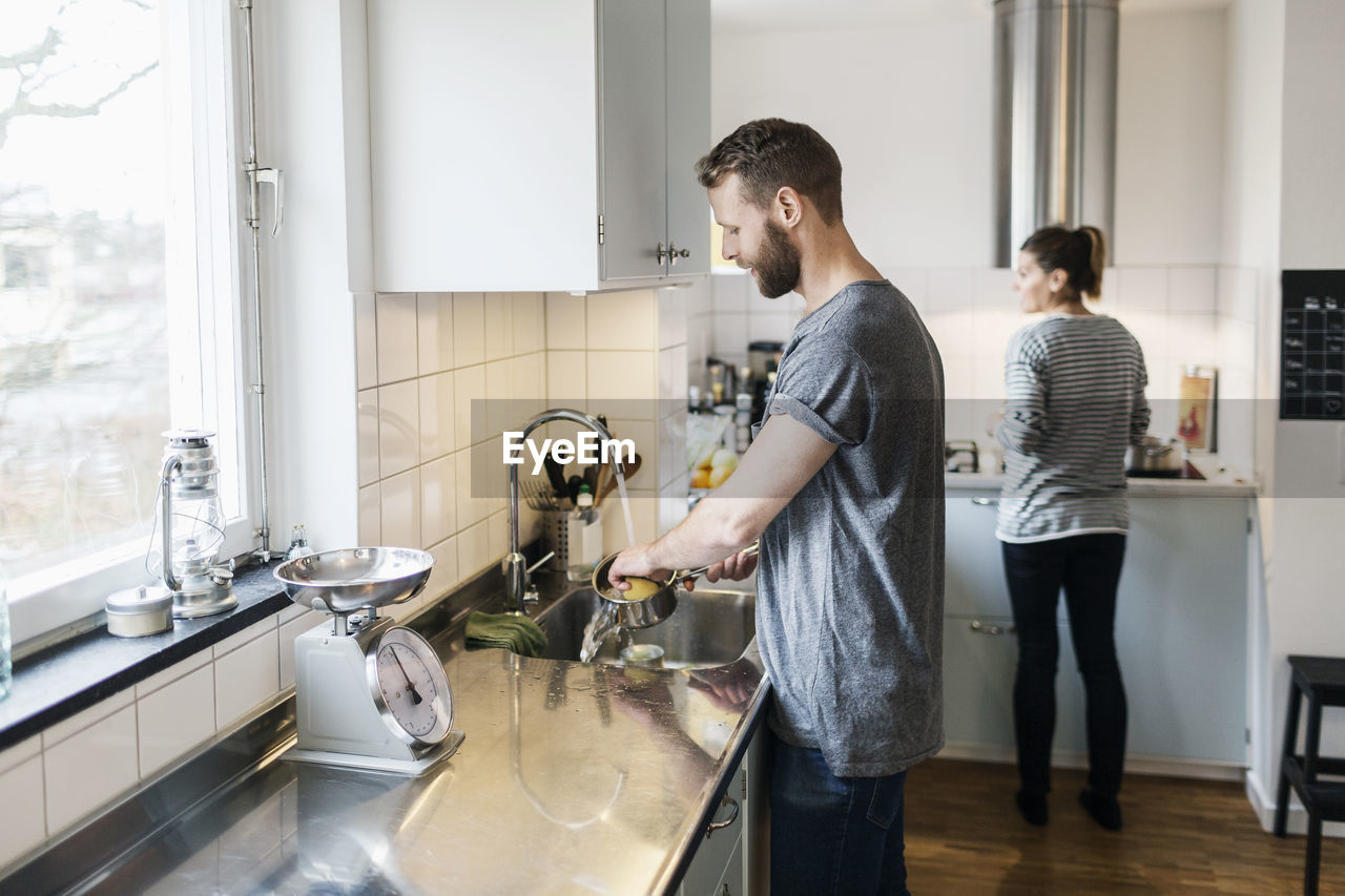 domestic room, kitchen, home, domestic kitchen, lifestyles, household equipment, indoors, sink, standing, domestic life, real people, faucet, young adult, casual clothing, adult, women, young men, men, cleaning, preparation, couple - relationship, preparing food