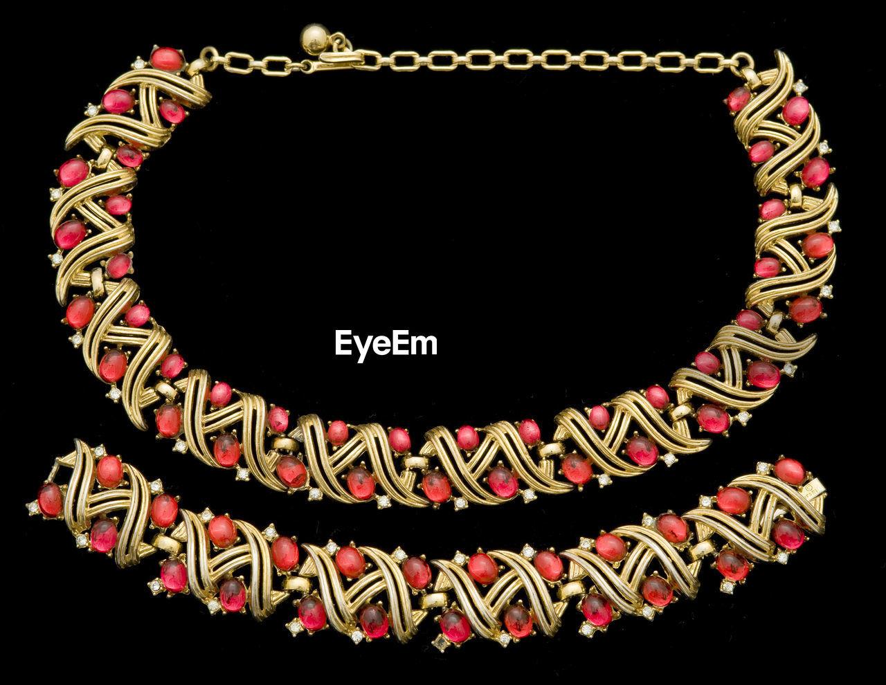 Close-Up Of Necklace And Bracelet Over Black Background