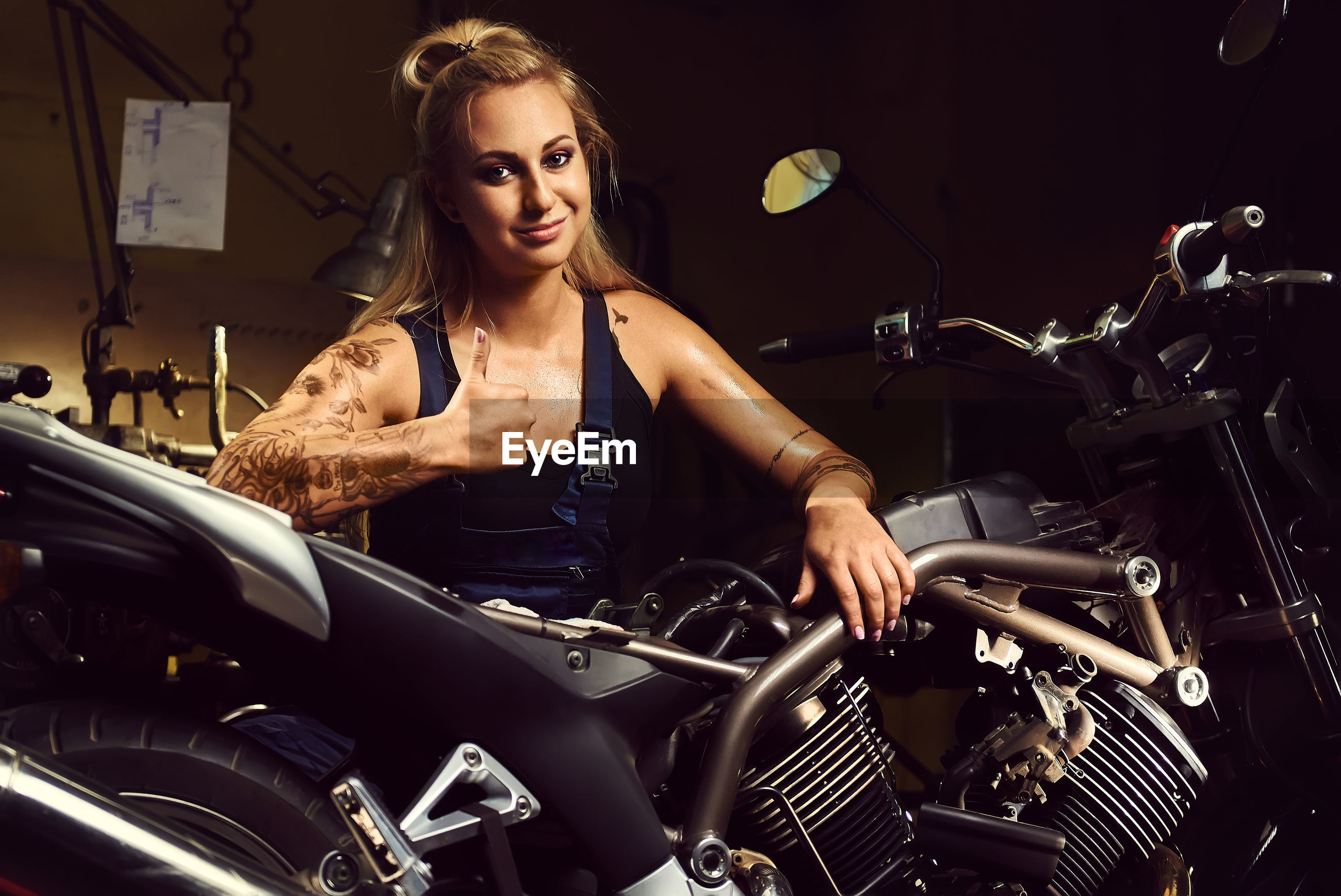 Portrait of female mechanic showing thumbs up in motorcycle workshop