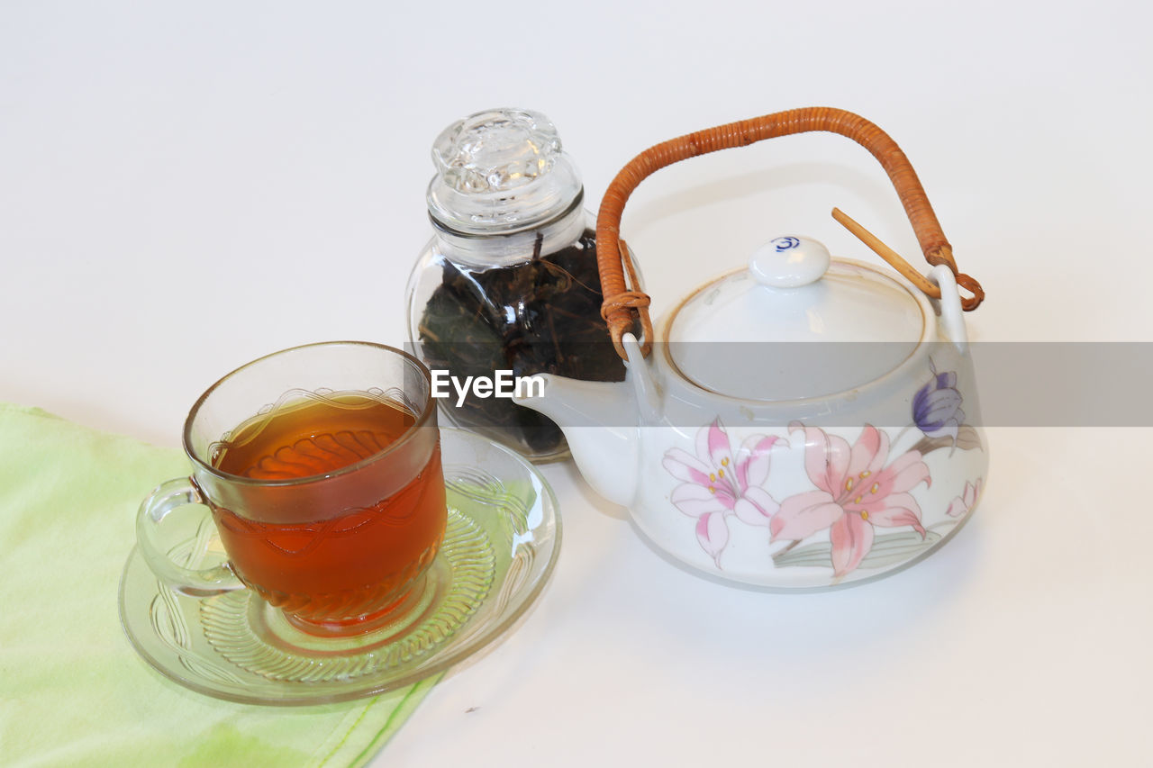 drink, refreshment, food and drink, indoors, teapot, still life, cup, tea, tea - hot drink, high angle view, hot drink, table, white background, studio shot, saucer, mug, no people, freshness, household equipment, glass, crockery, tea cup, floral pattern