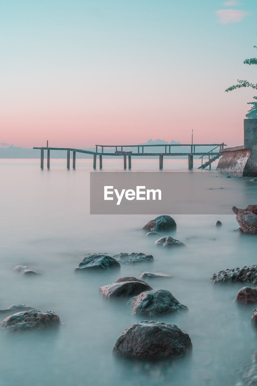 water, sky, sea, rock, solid, sunset, scenics - nature, beauty in nature, nature, rock - object, tranquility, bridge, tranquil scene, long exposure, connection, bridge - man made structure, built structure, no people, waterfront, outdoors, horizon over water, flowing water