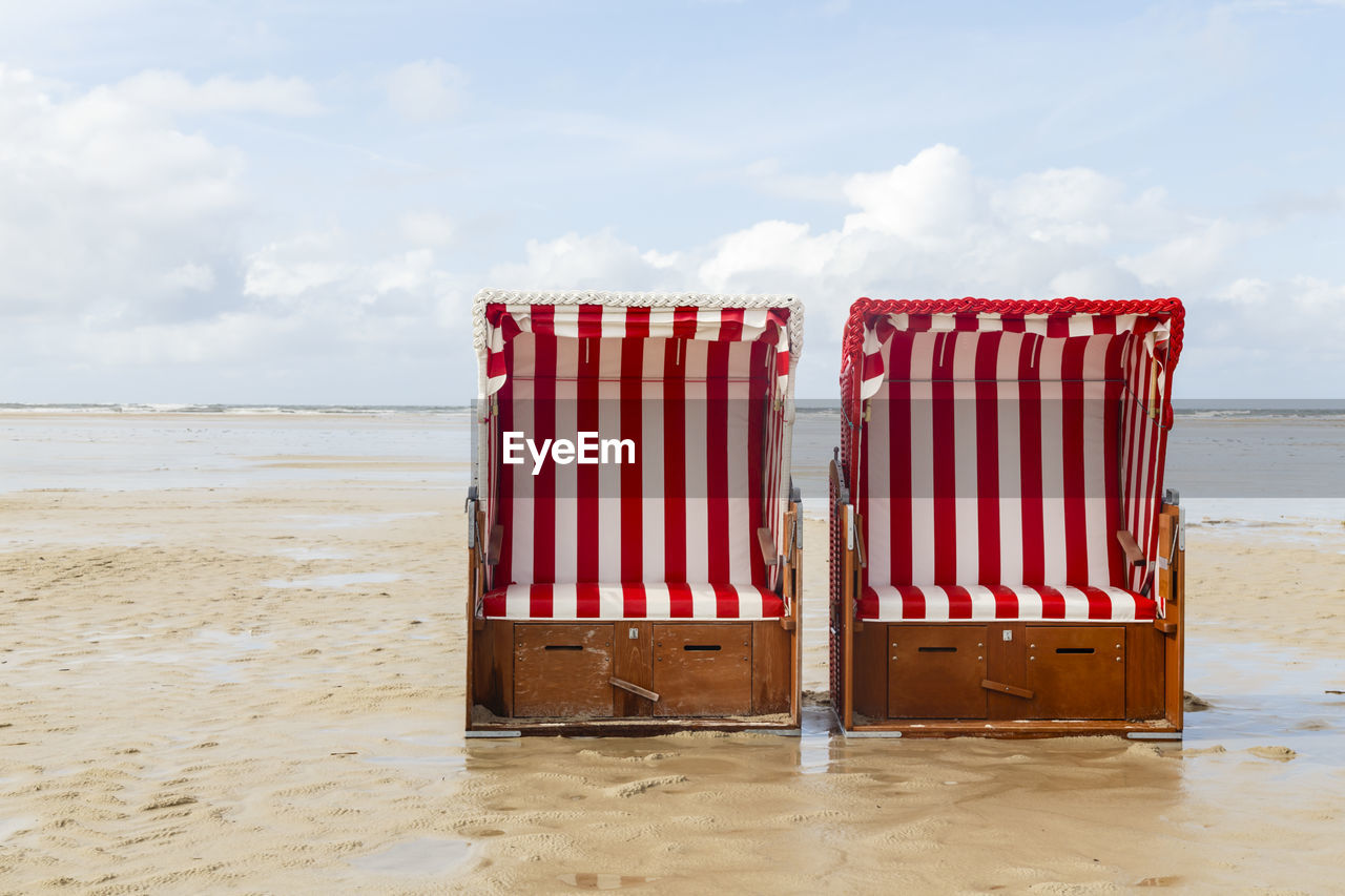 beach, land, sky, sea, sand, cloud - sky, striped, water, nature, day, hooded beach chair, beauty in nature, no people, outdoors, sunlight, tranquility, red, container, scenics - nature