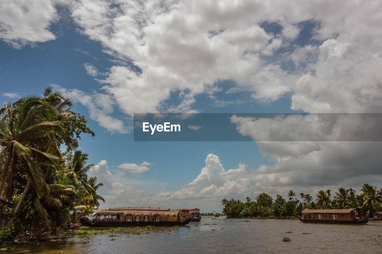 Boathouses In Backwaters Against Cloudy Sky