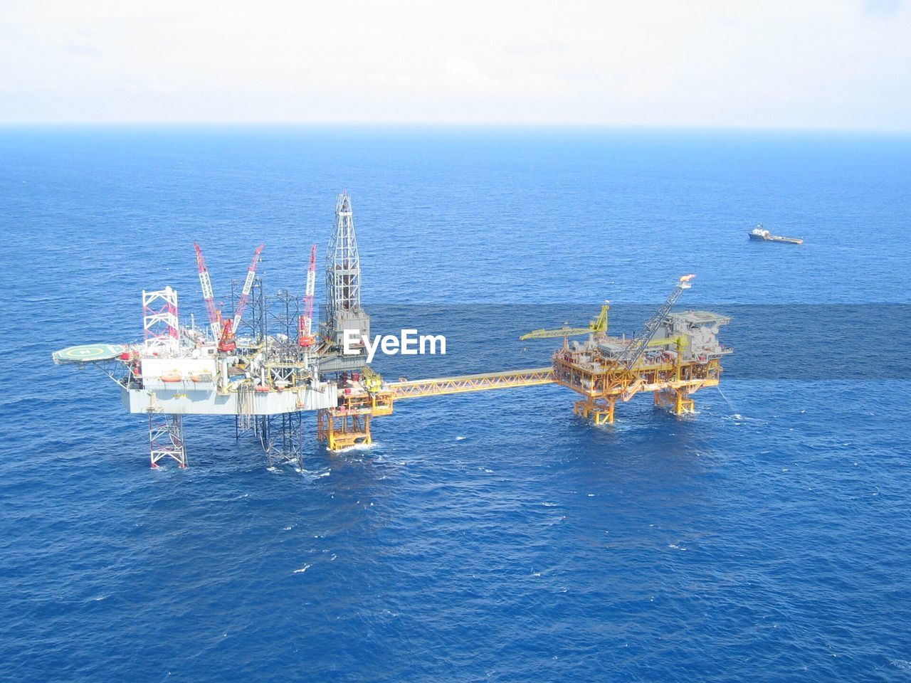 SCENIC VIEW OF OIL DRILL IN SEA AGAINST CLEAR SKY