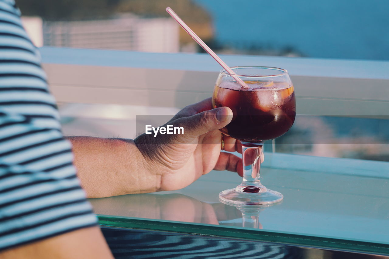 Close-up of hand holding drink on table