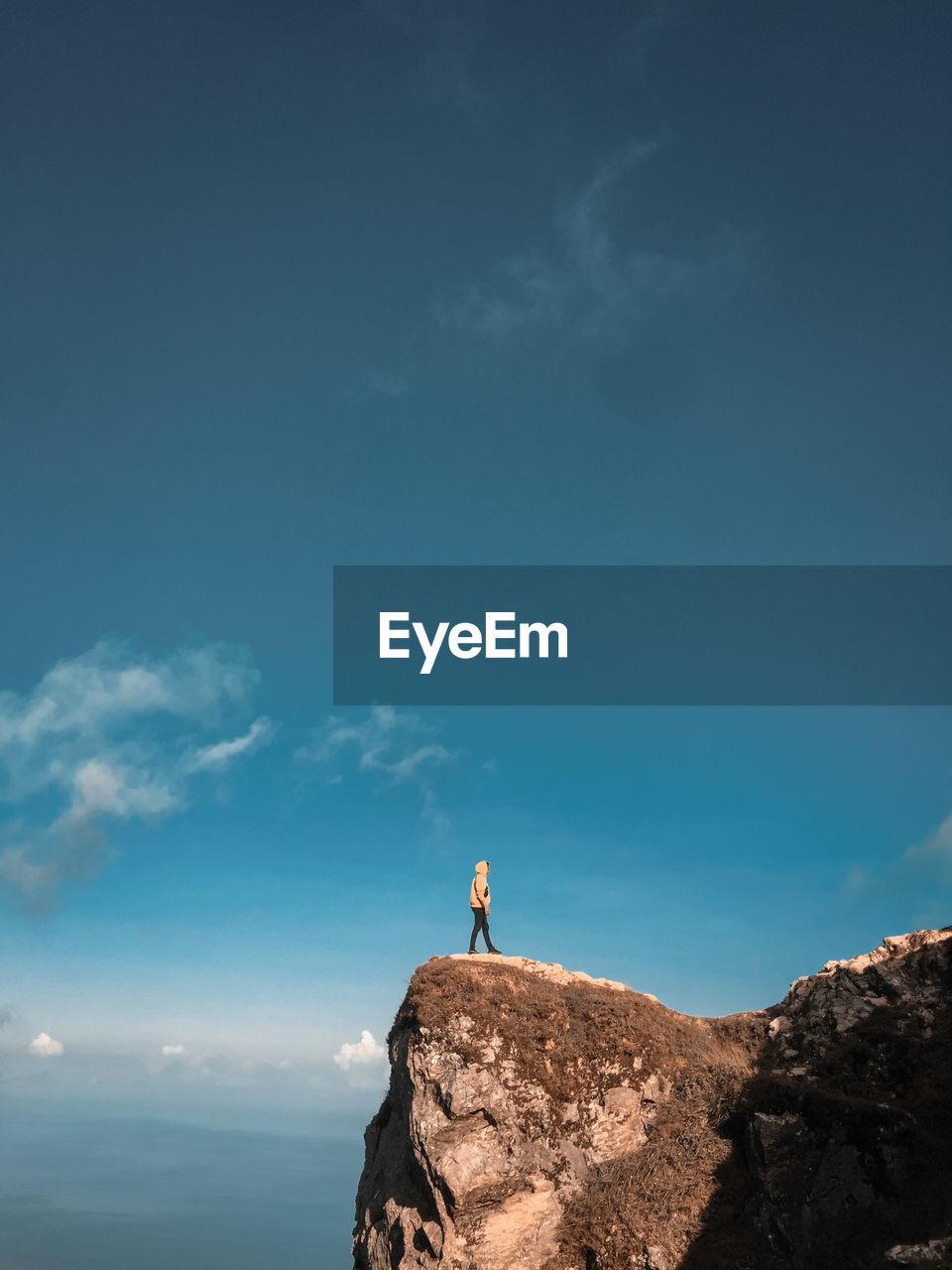 Full length of man standing at cliff against sky