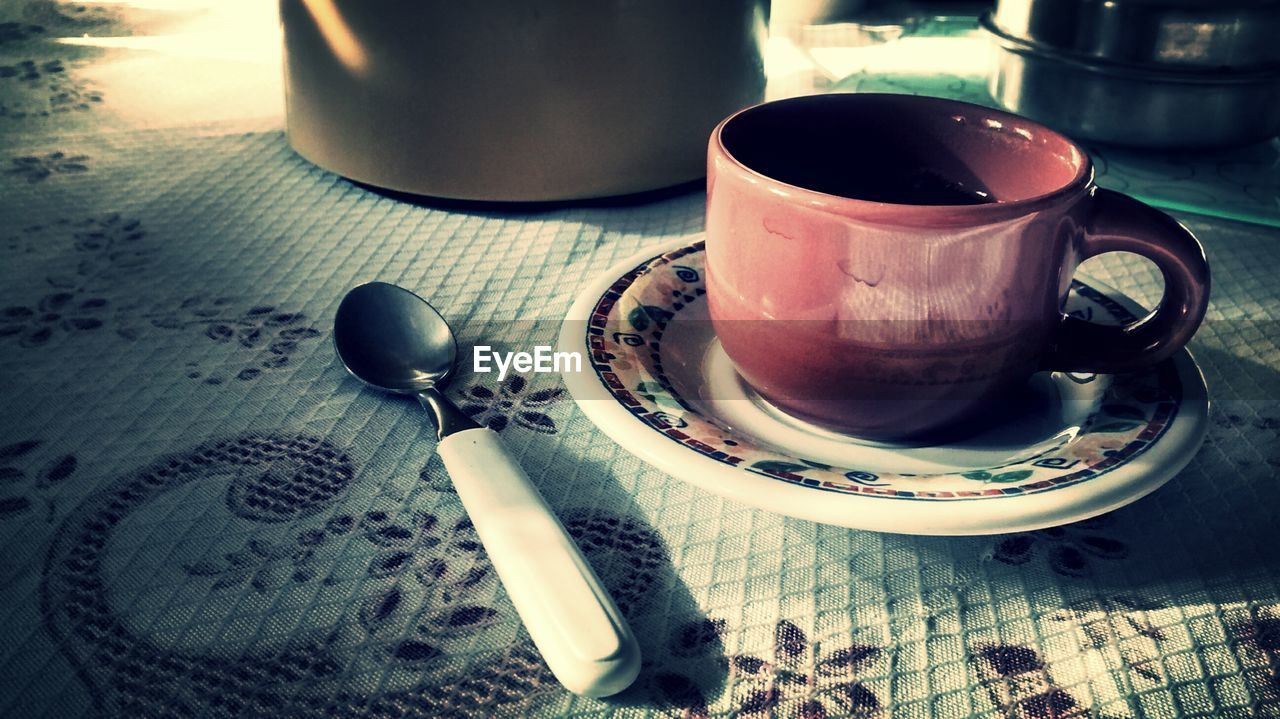 Cup and saucer by spoon on table