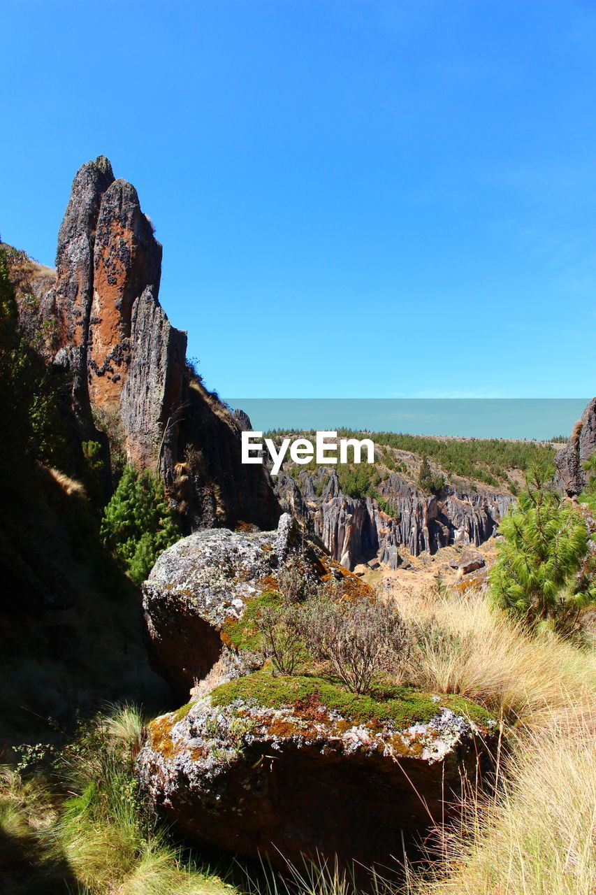 rock - object, rock formation, nature, tranquil scene, tranquility, scenics, beauty in nature, geology, blue, day, no people, clear sky, sunlight, outdoors, physical geography, landscape, cliff, travel destinations, sky, grass, tree