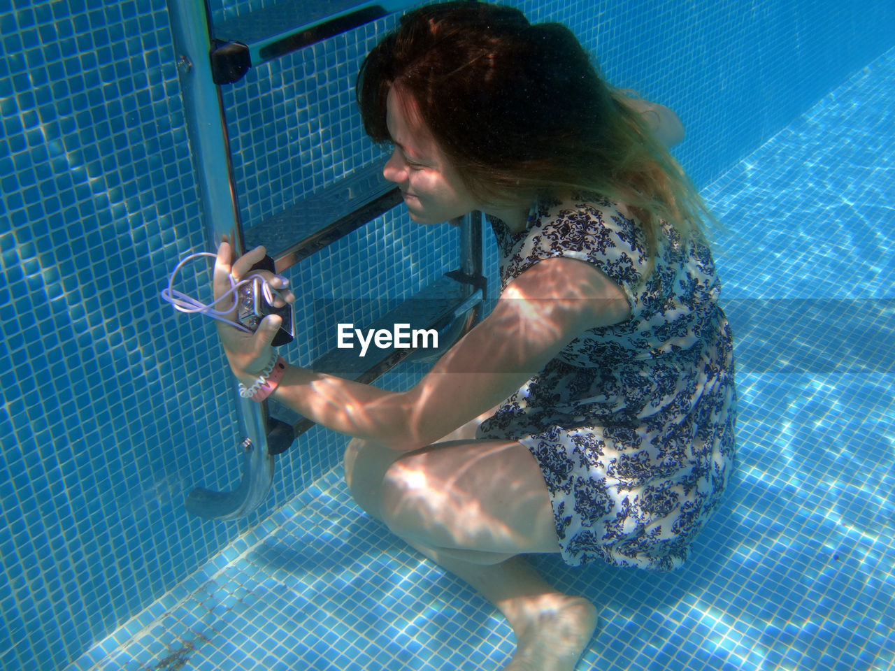 Young woman with technology in swimming pool