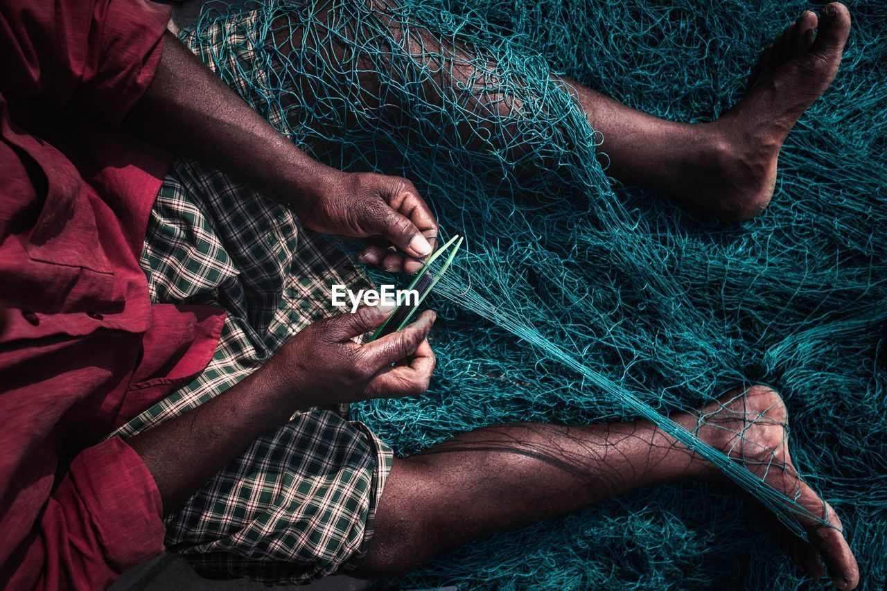 real people, men, midsection, holding, people, hand, human hand, human body part, connection, high angle view, two people, working, adult, occupation, textile, day, technology, wireless technology, fishing net
