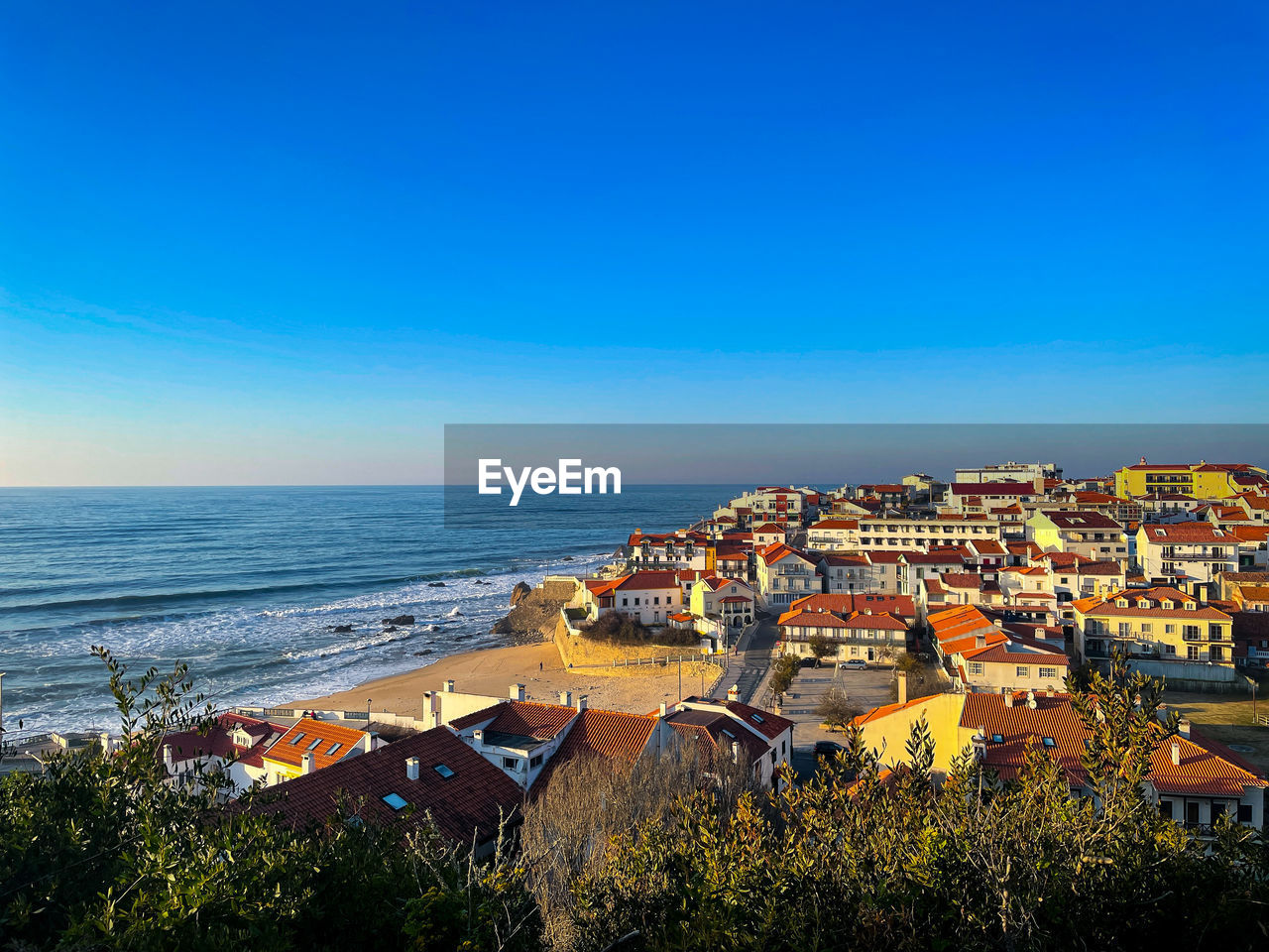 HIGH ANGLE SHOT OF TOWNSCAPE BY SEA AGAINST CLEAR SKY