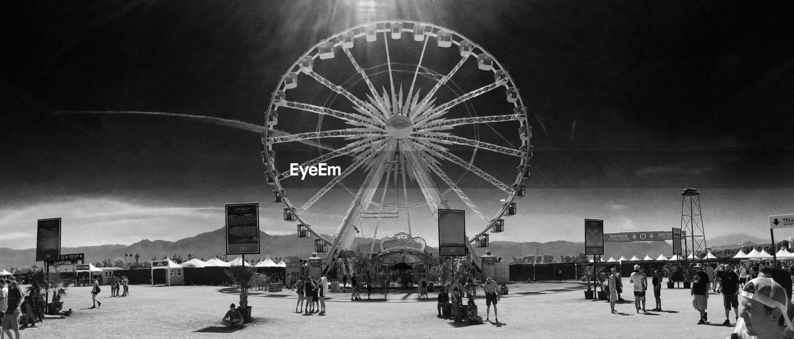 large group of people, arts culture and entertainment, amusement park, amusement park ride, sky, leisure activity, ferris wheel, lifestyles, architecture, built structure, person, men, enjoyment, fun, building exterior, illuminated, cloud - sky, mixed age range, tourism