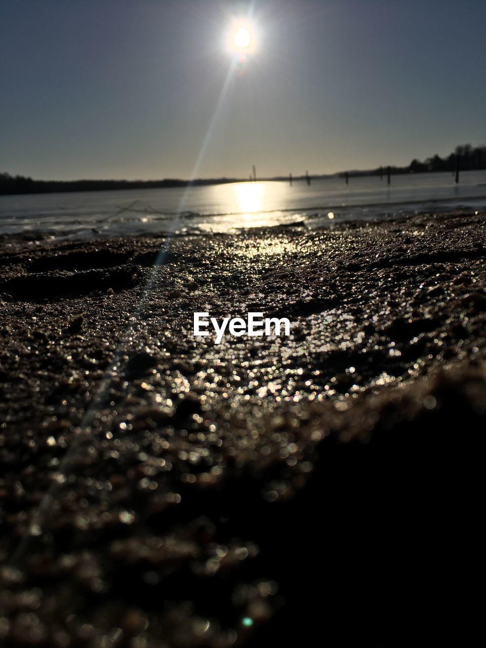 water, nature, beauty in nature, beach, sun, scenics, tranquility, sea, lens flare, sunlight, sky, shore, tranquil scene, outdoors, sunset, reflection, sand, no people, horizon over water, clear sky, day, close-up, pebble beach