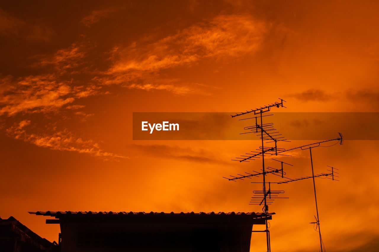 Low angle view of silhouette antenna against sky during sunset