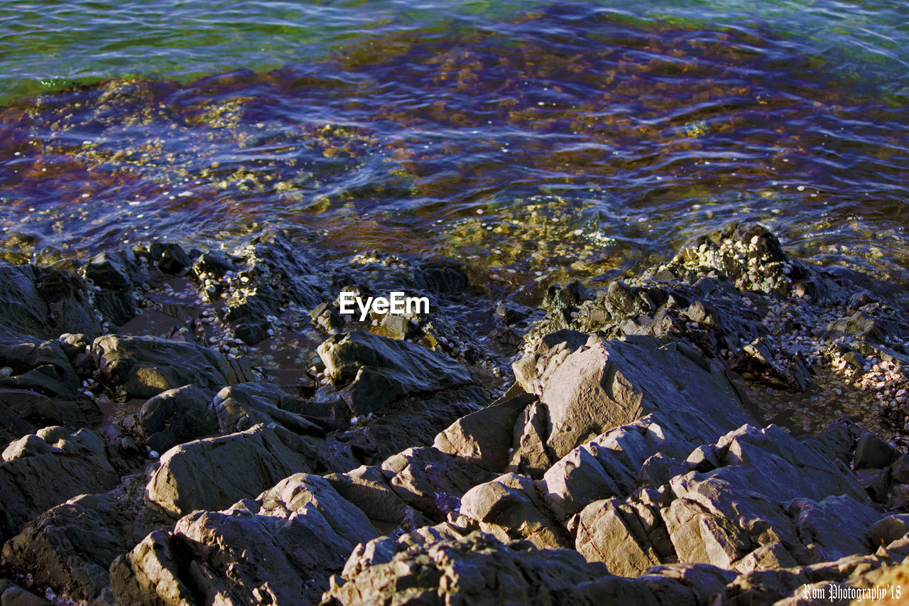 water, nature, sea, no people, rock, day, land, solid, beauty in nature, beach, rock - object, tranquility, high angle view, outdoors, full frame, sunlight, rippled, motion, pollution, flowing water