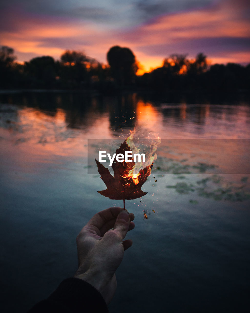 Cropped Hand Holding Burning Autumn Leaf Against Lake During Sunset