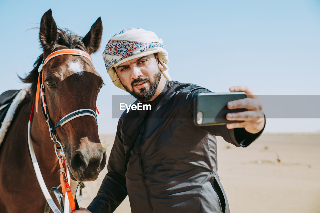 Young Man Taking Selfie With Mobile Phone Riding Horse At Desert