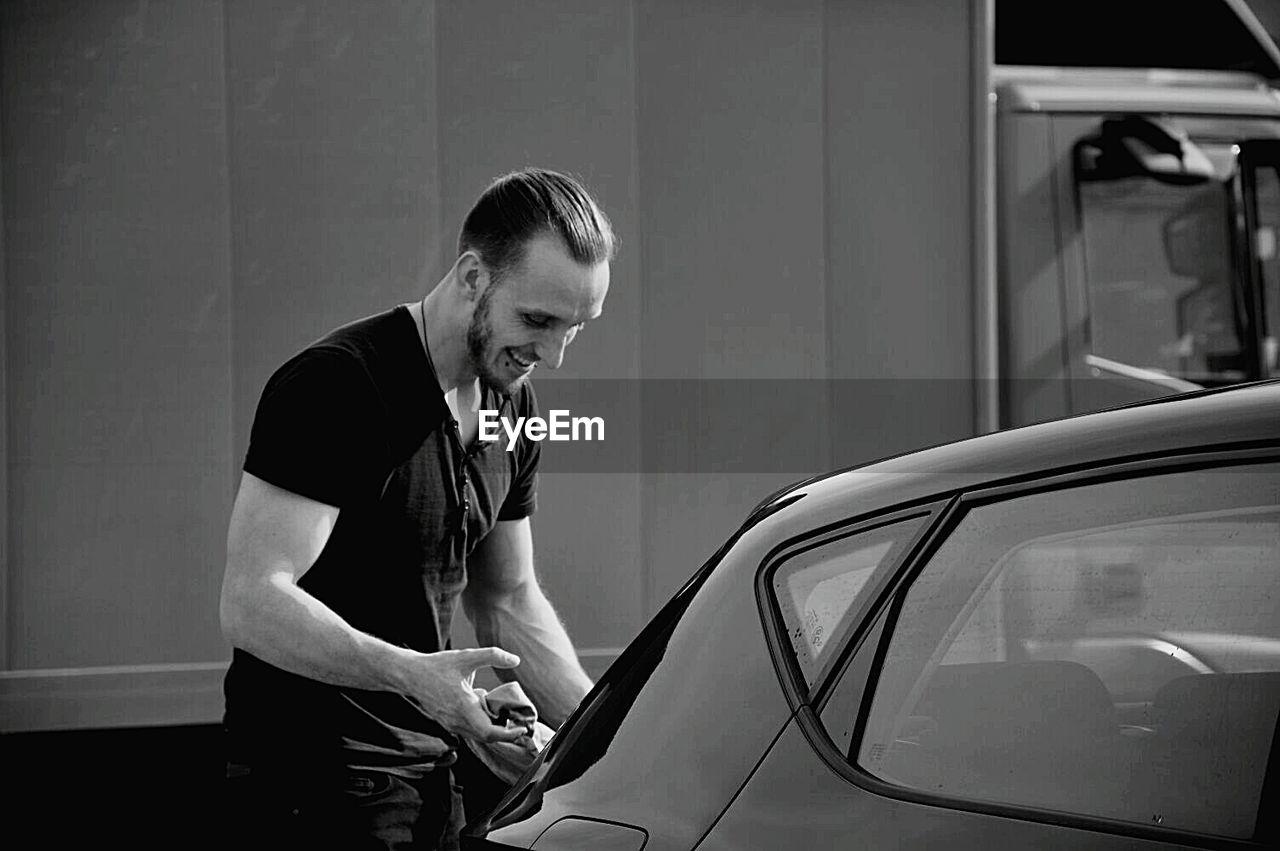 Smiling Man Washing Car
