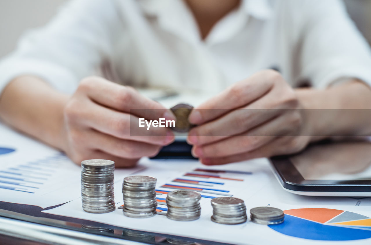 Midsection of businessman with stacked coins at desk in office