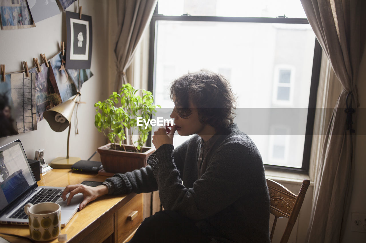 one person, real people, side view, technology, indoors, home interior, casual clothing, lifestyles, sitting, table, communication, wireless technology, window, furniture, young adult, waist up, young men, computer, connection, hairstyle