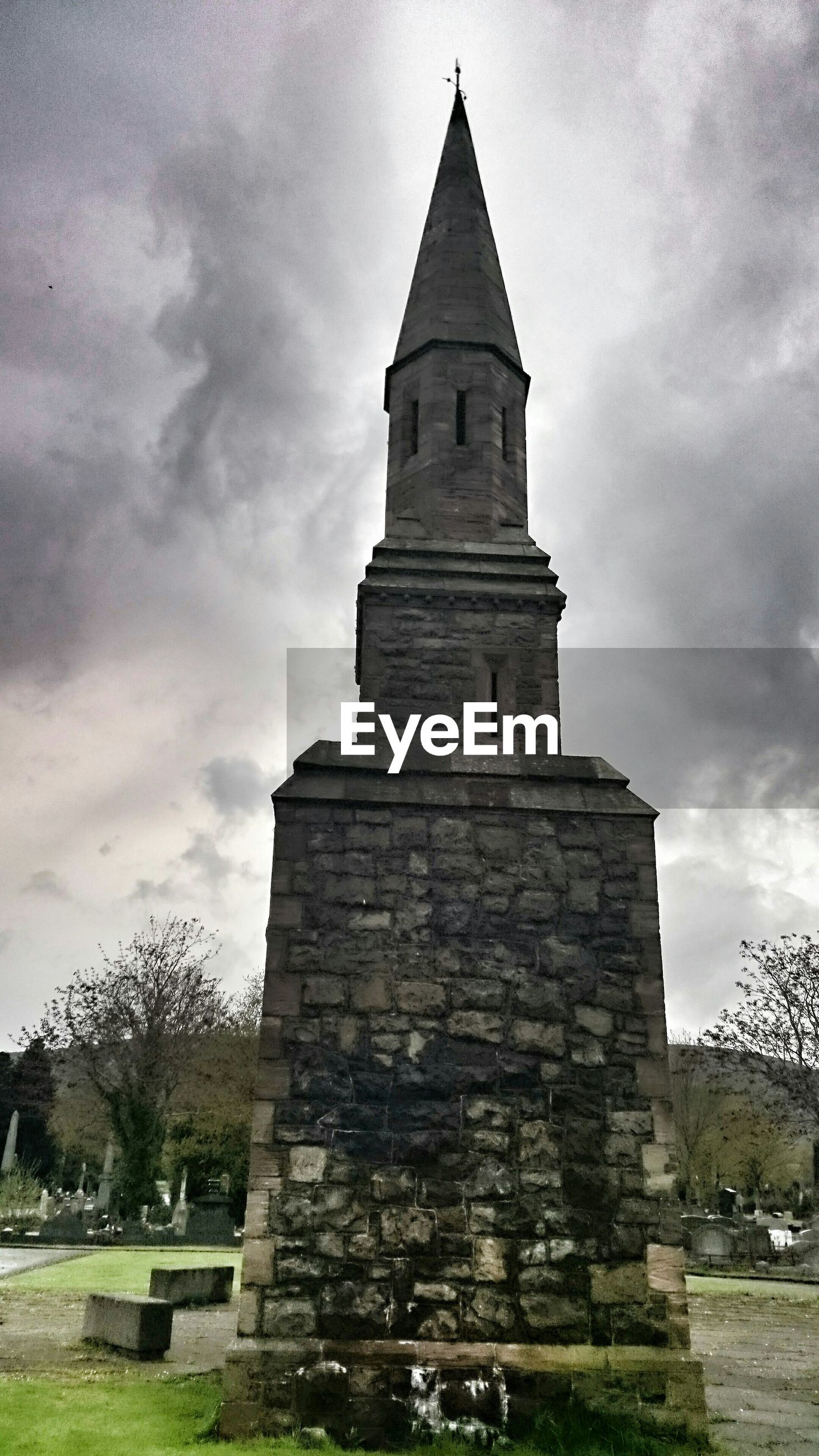 Low angle view of old building in cemetery against cloudy sky