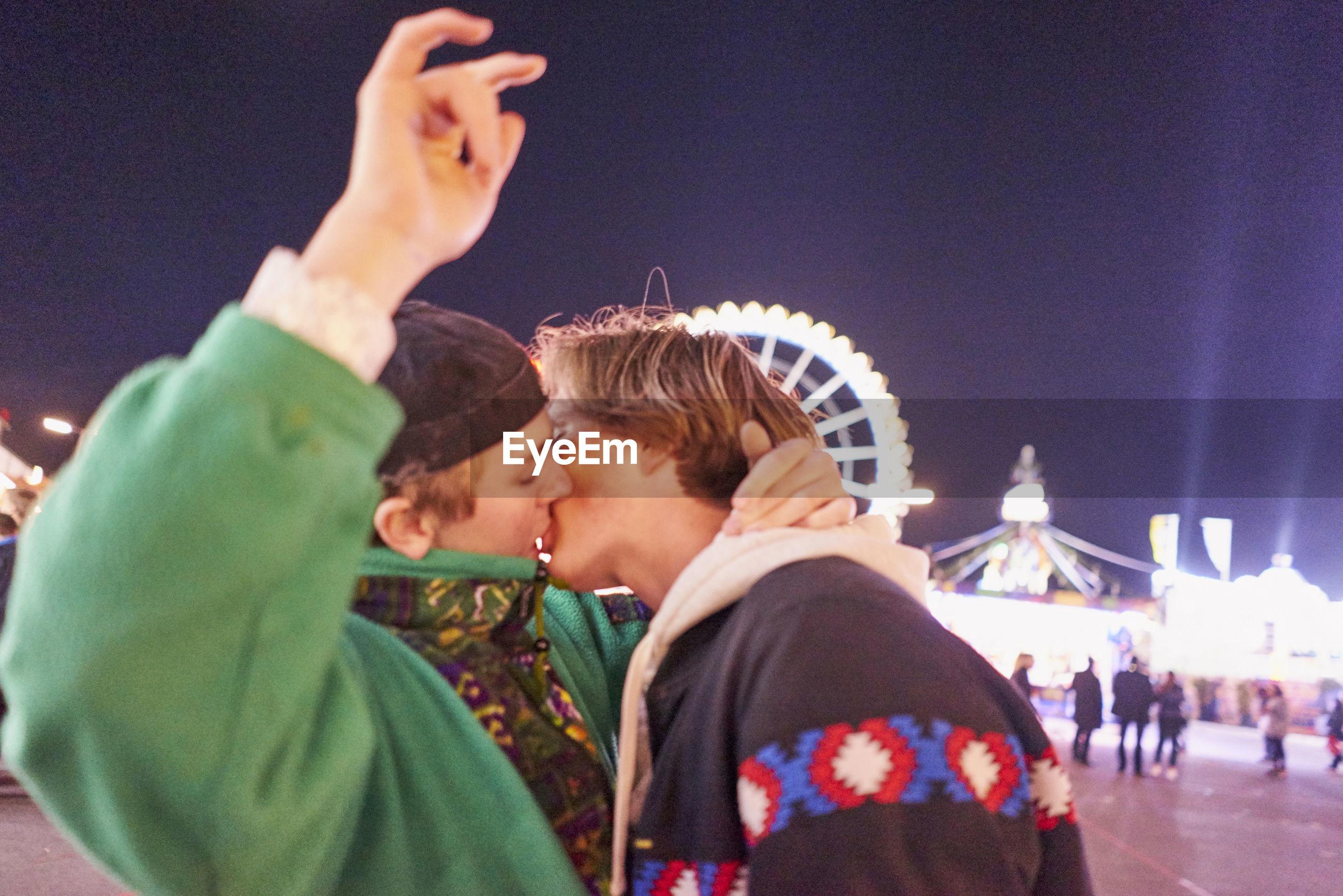 Gay men kissing at amusement park during night