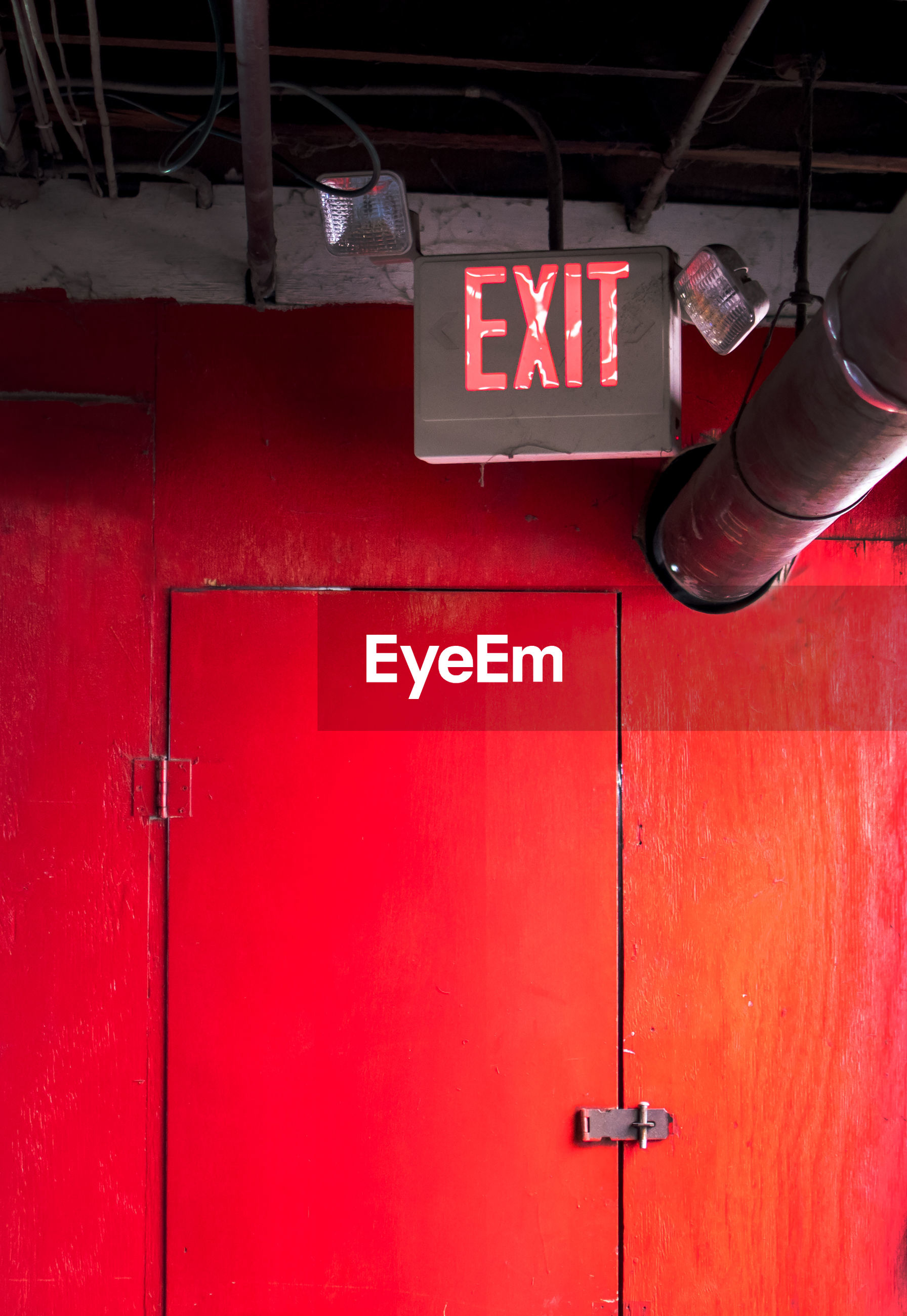 Emergency exit sign with bright light, over a red door in a factory