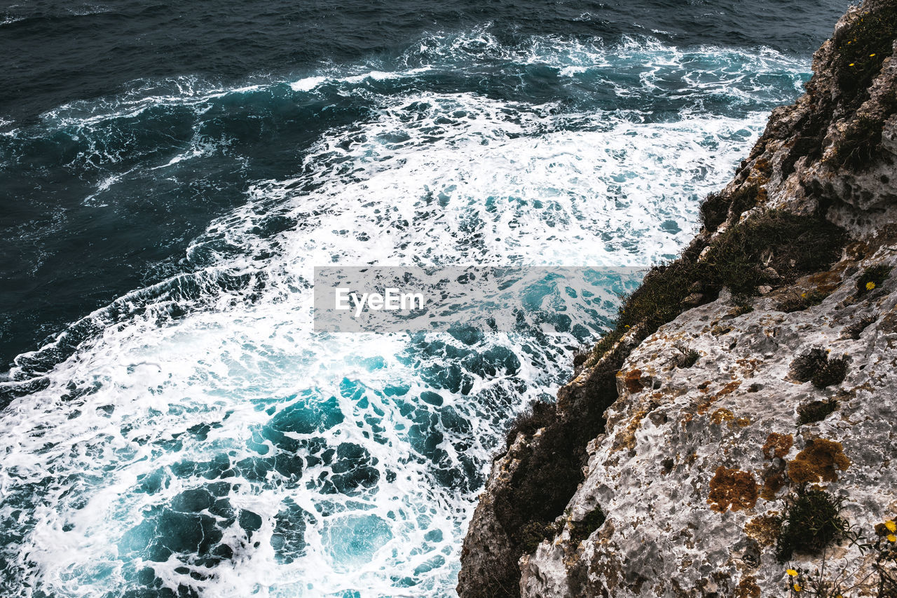 water, sea, motion, wave, rock, sport, aquatic sport, beauty in nature, rock - object, surfing, solid, nature, splashing, day, high angle view, scenics - nature, power in nature, land, outdoors, breaking, rocky coastline