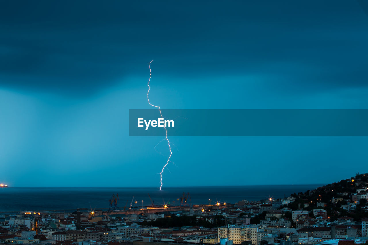 Lightning Over Sea By City At Dusk