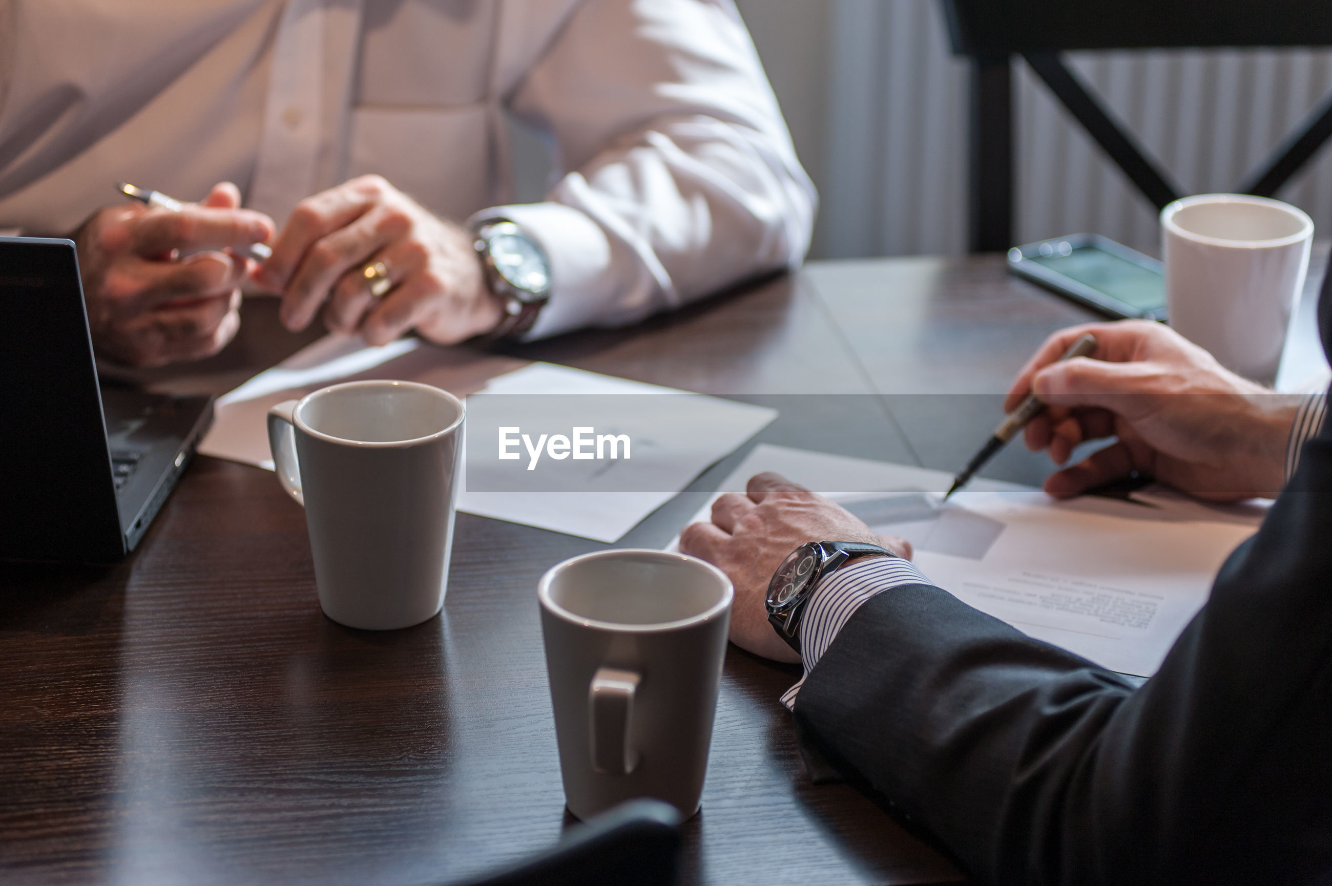 Midsection of business people working with coffee cups on desk at office