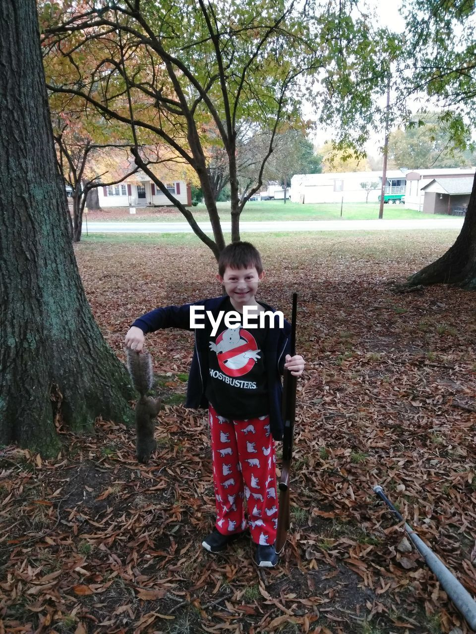 tree, field, looking at camera, front view, real people, portrait, smiling, standing, outdoors, childhood, full length, one person, day, halloween