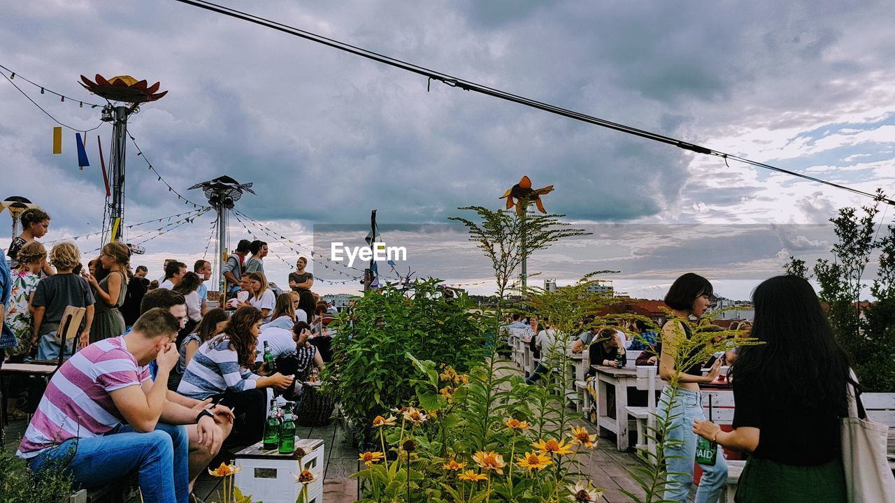 real people, sitting, sky, togetherness, cloud - sky, men, women, leisure activity, connection, day, outdoors, lifestyles, enjoyment, communication, casual clothing, large group of people, chair, wireless technology, technology, young women, crowd, nature, friendship, young adult, adult, people