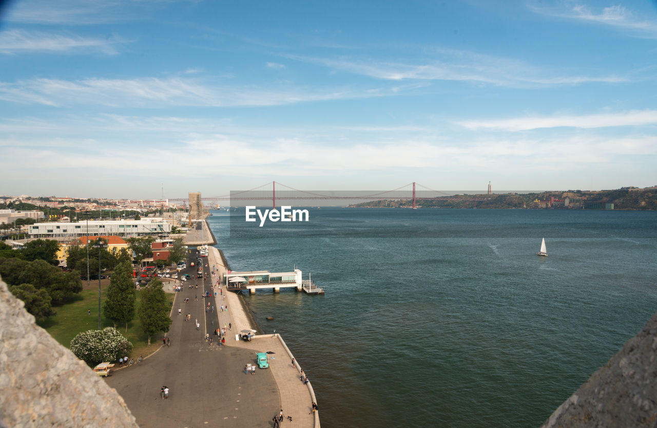 architecture, built structure, transportation, building exterior, bridge - man made structure, city, water, suspension bridge, sky, connection, high angle view, travel destinations, day, outdoors, sea, cloud - sky, no people, cityscape, nature, tree