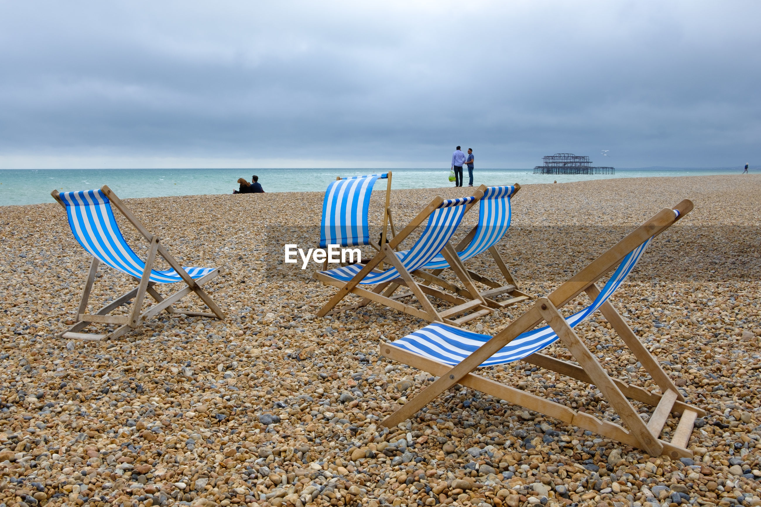 Deck chairs at beach against cloudy sky